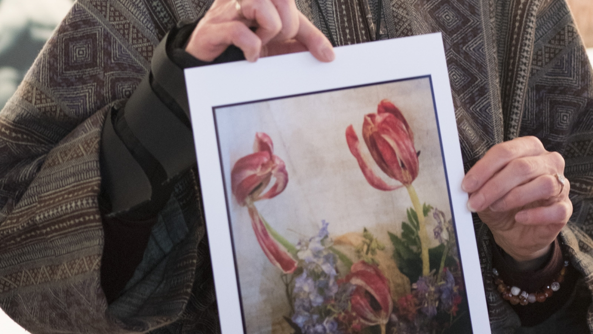 Floyd Photo Gallery Exhibitor Rosemary Polletta holds one of her artwork at The Floyd Photo Gallery